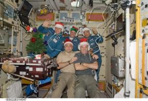 Astronauter der fejrer jul. Bemærk guldkorset over deres hoveder, samt Jesus til venstre øverst og helgenbilledet under Jesus, desuden Taj Mahal til højre (©NASA).
